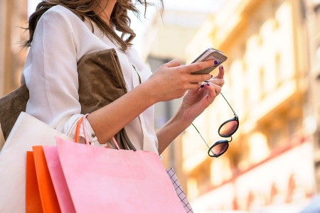 Women carrying shoppings bags and using smartphone, Retail, Shopping, Women, designer sales, womens fashion, sale deals, how to shop during sale time, sale tips, Only Women, Fashion, texting, smartphone, city